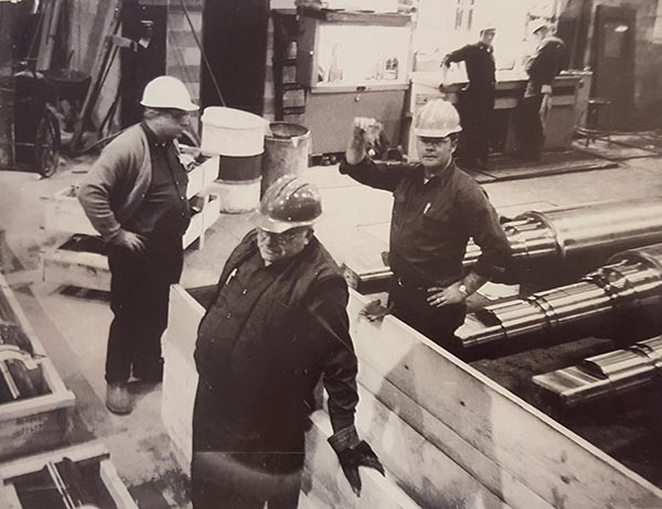 Circa 1974. Russ and Gene Eaborn with the Shipper determining how they are going to load and place a large rolling mill roll on the trailer.